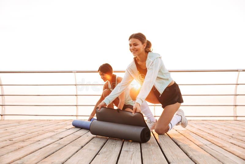 Twee vrienden van sportenvrouwen in openlucht op het strand met tapijt royalty-vrije stock afbeelding