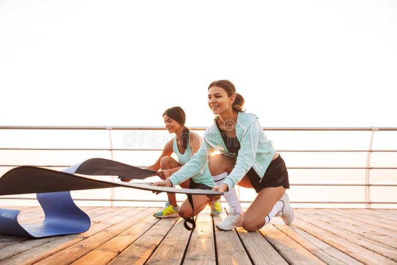 Twee vrienden van sportenvrouwen in openlucht op het strand met tapijt royalty-vrije stock foto's