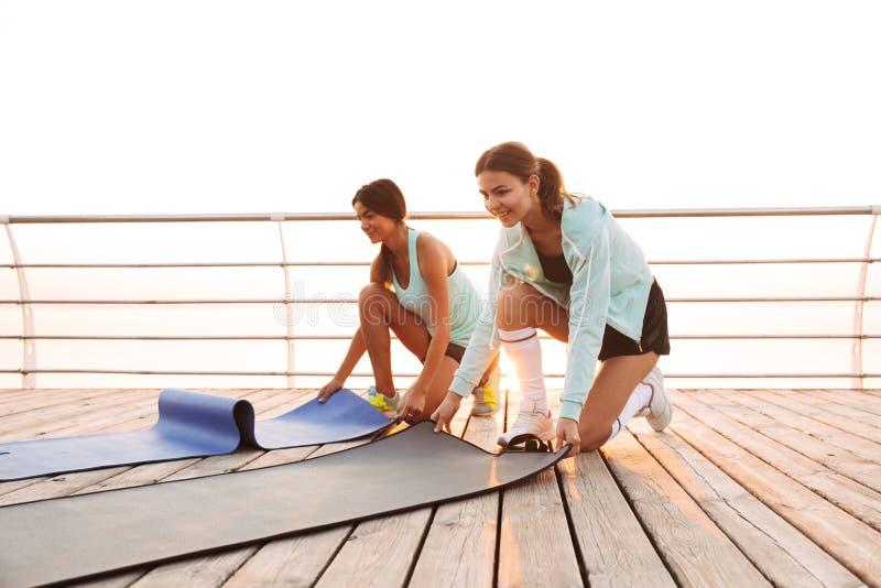 Twee vrienden van sportenvrouwen in openlucht op het strand met tapijt stock afbeelding