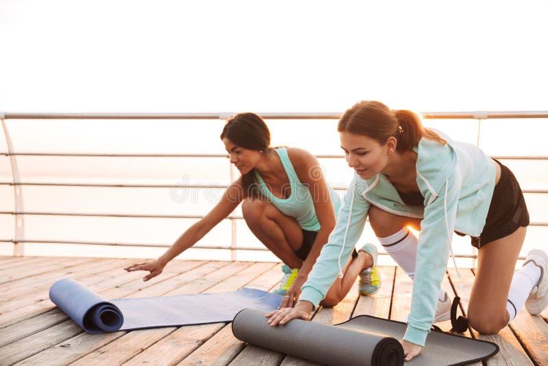Twee vrienden van sportenvrouwen in openlucht op het strand met tapijt royalty-vrije stock afbeeldingen
