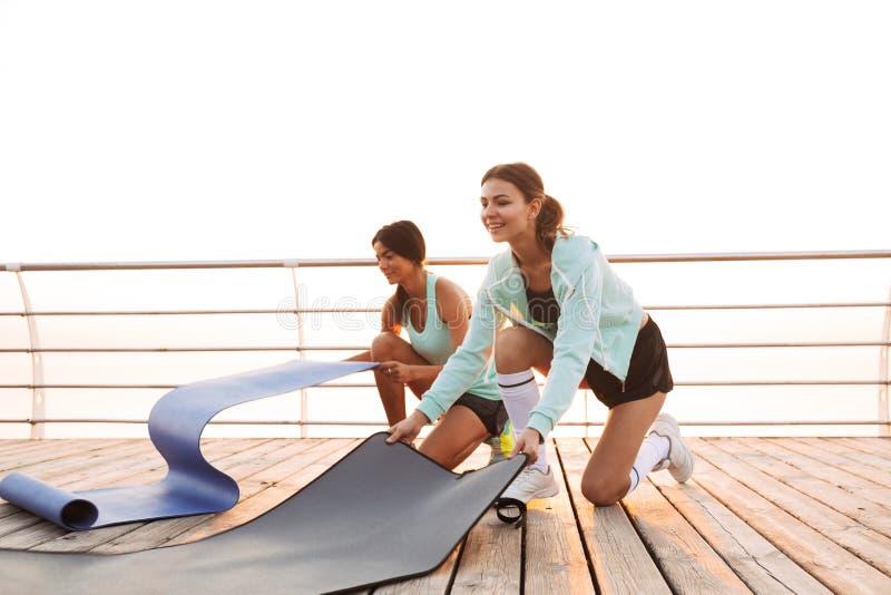 Twee vrienden van sportenvrouwen in openlucht op het strand met tapijt royalty-vrije stock fotografie