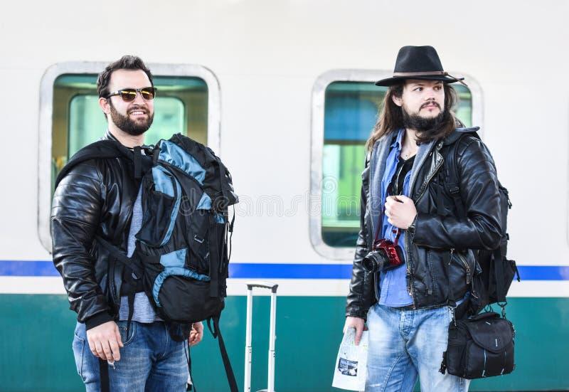 Twee vrienden wachten op de trein te komen stock afbeelding