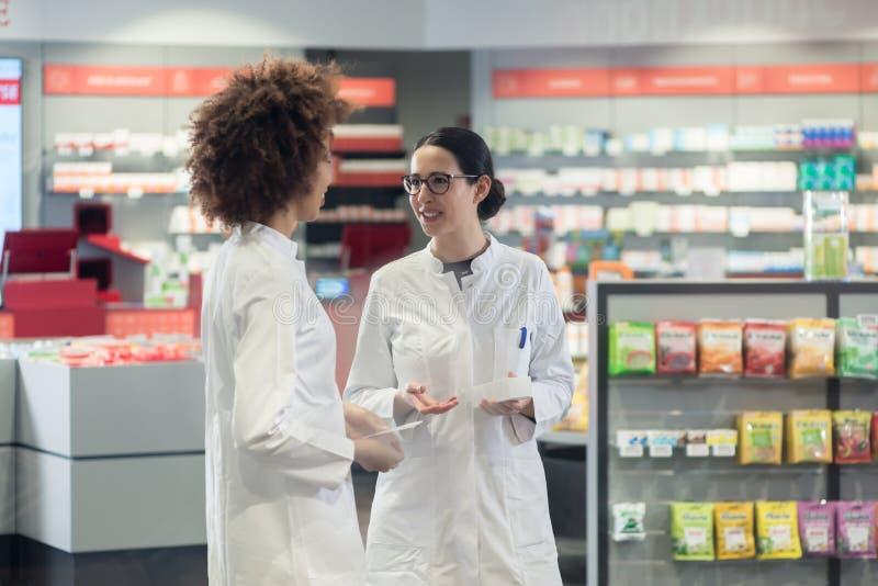 Twee vriendschappelijke collega's die terwijl het samenwerken in een moderne drogisterij spreken royalty-vrije stock afbeeldingen