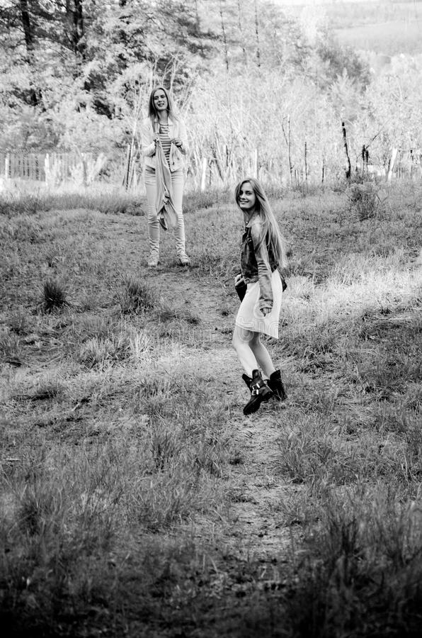 Twee vrij jonge tweelingenmeisjes die op de plattelandsweg lopen royalty-vrije stock afbeelding