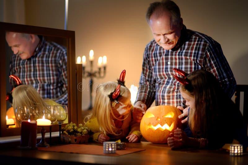 Twee vrij jonge zusters in Halloween-kostuums en hun opa die een pompoen samen snijden stock afbeeldingen