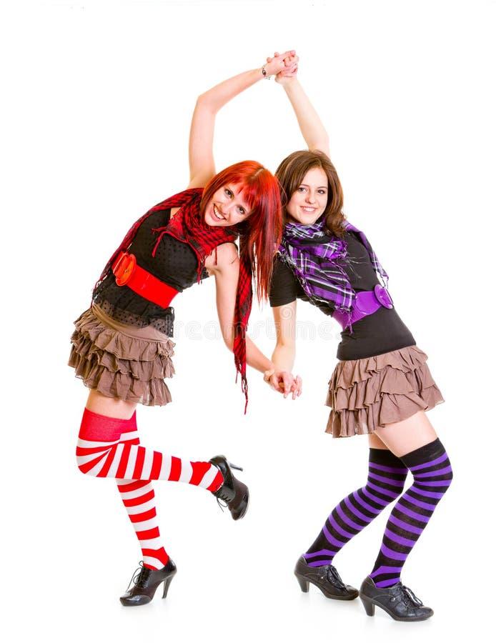 Twee vrij vrolijke meisjes die zich rijtjes bevinden stock foto