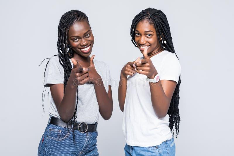Twee vrolijke Afrikaanse meisjes die vingers richten op camera hey betekenen u isoleerden over witte achtergrond royalty-vrije stock afbeelding