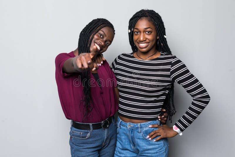Twee vrolijke Afrikaanse meisjes die vingers richten op camera hey betekenen u isoleerden over witte achtergrond stock foto