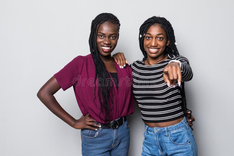 Twee vrolijke Afrikaanse meisjes die vingers richten op camera hey betekenen u isoleerden over witte achtergrond stock afbeeldingen