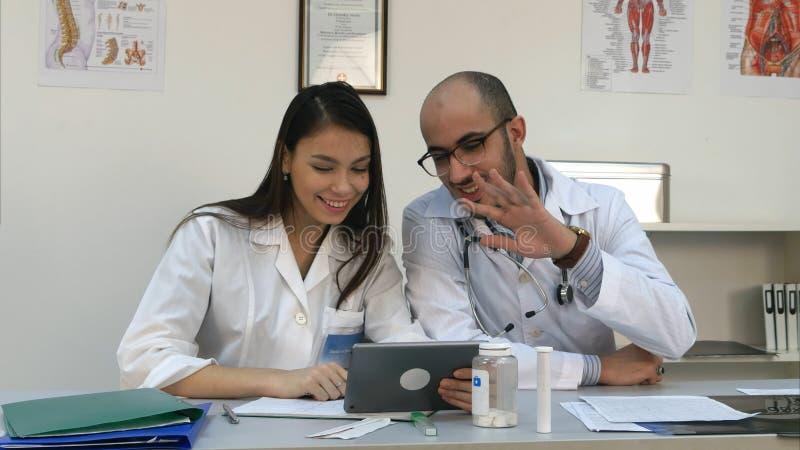 Twee vrolijke artsen die positieve videovraag via tablet hebben stock foto