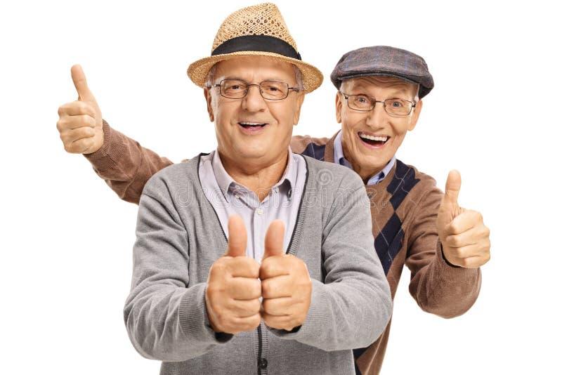 Twee vrolijke bejaarden die hun duimen tegenhouden stock foto