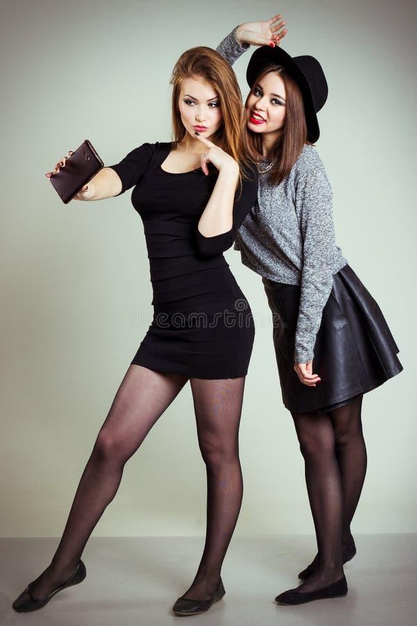 Twee vrolijke gelukkige die meisjesmeisjes op de telefoon, Zelftelefoon worden gefotografeerd stock foto