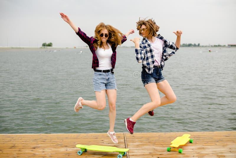 Twee vrolijke gelukkige schaatsermeisjes in hipsteruitrusting die pret op een houten pijler hebben tijdens de zomervakantie royalty-vrije stock fotografie