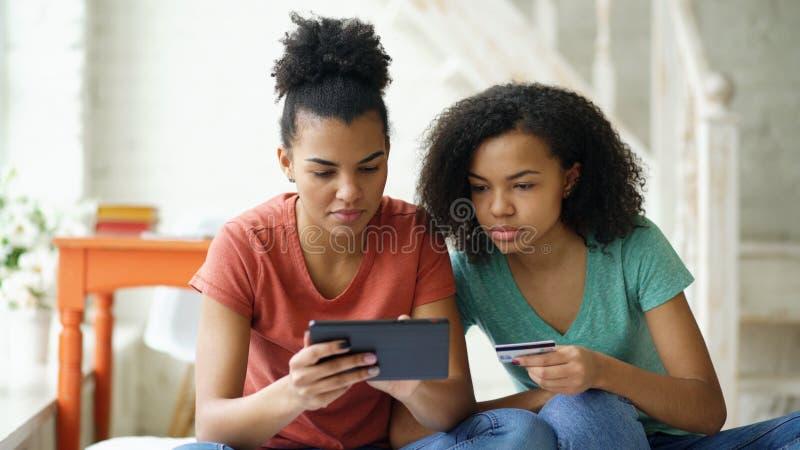 Twee vrolijke gemengde ras krullende meisjes die online met tabletcomputer en creditcard thuis winkelen stock foto