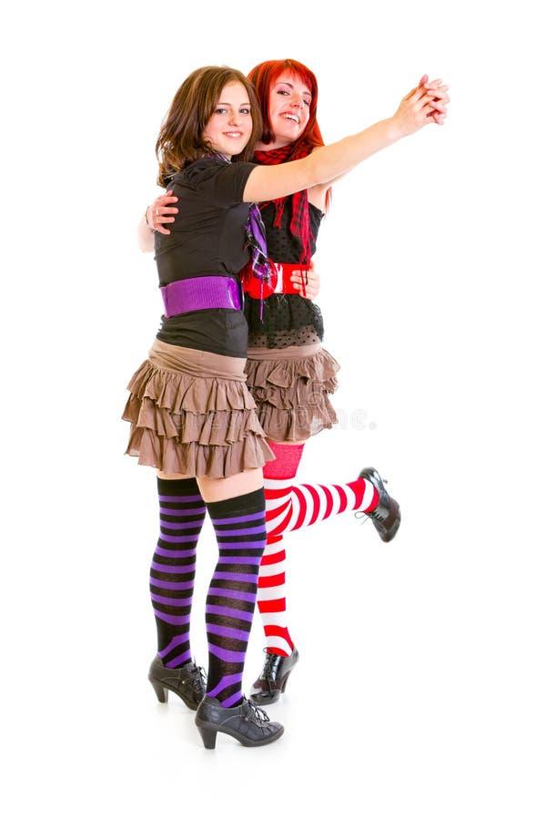Twee vrolijke jonge meisjes die voor pret dansen stock afbeelding