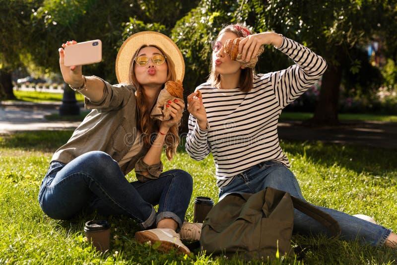 Twee vrolijke jonge meisjesvrienden die pret hebben bij het park royalty-vrije stock afbeelding
