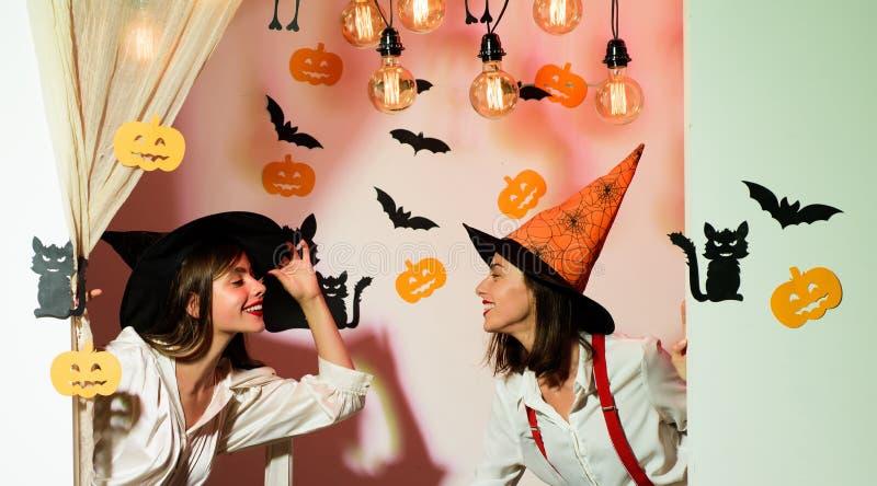 Twee vrolijke jonge vrouwen in de kostuums van heksenhalloween het dansen Halloween-partijmeisje Vieringenkleding en heks stock afbeelding