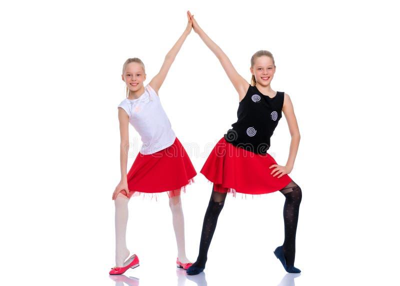 Twee vrolijke meisjes dansen stock afbeeldingen
