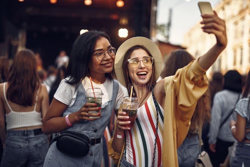 Twee vrolijke meisjes die met cocktails selfie maken royalty-vrije stock foto's