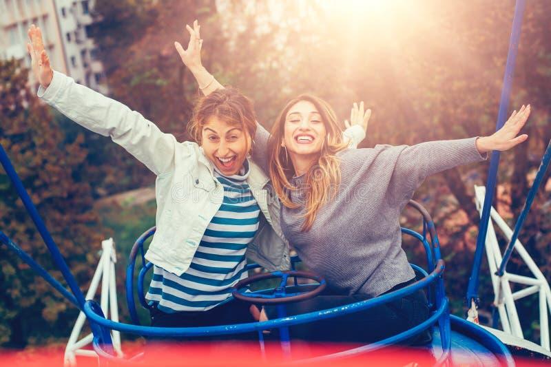 Twee vrolijke meisjes die pret op vrolijk hebben gaan rond royalty-vrije stock afbeeldingen