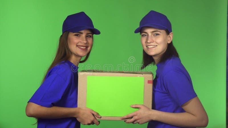 Twee vrolijke vrouwelijke arbeiders die van de leveringsdienst de doos van het holdingskarton glimlachen stock afbeeldingen