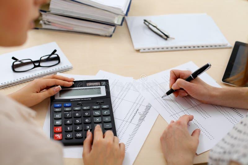 Twee vrouwelijke accountants die op calculatorinkomen tellen voor de close-up van de voltooiingshanden van de belastingsvorm De d royalty-vrije stock afbeelding