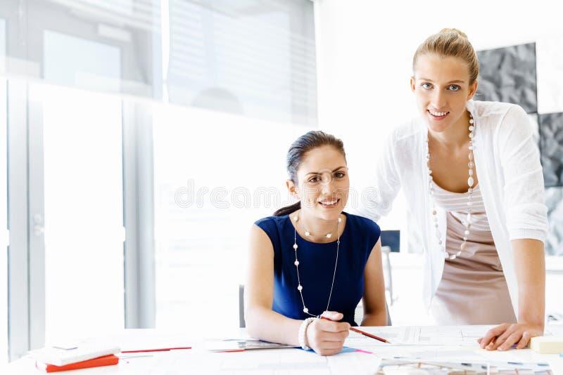 Twee vrouwelijke collega's in bureau stock afbeeldingen