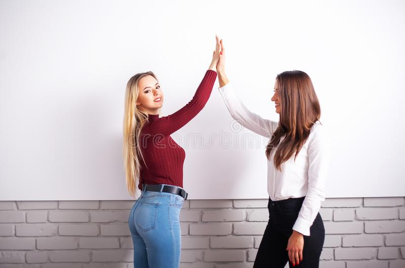 Twee vrouwelijke collega's in bureau die samenwerken Twee vrouwelijke collega's in bureau die samenwerken stock foto's