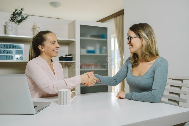 Twee vrouwelijke collega's die samen met laptop in het bureau werken stock afbeeldingen