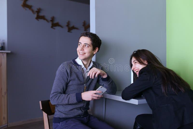 Twee vrouwelijke en mannelijke werknemers bespreken het werk en zitten in bureau onderzoek royalty-vrije stock foto's