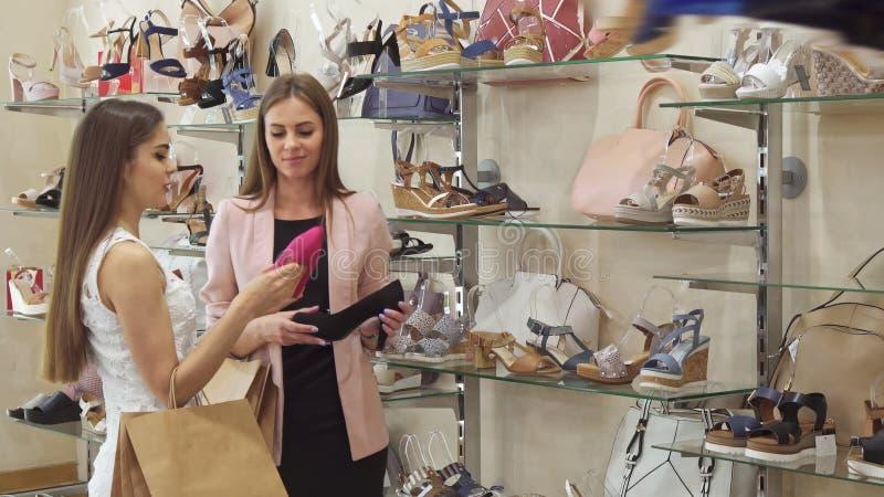 Twee vrouwelijke kopers kiezen hoge hielschoenen bij de winkel stock foto