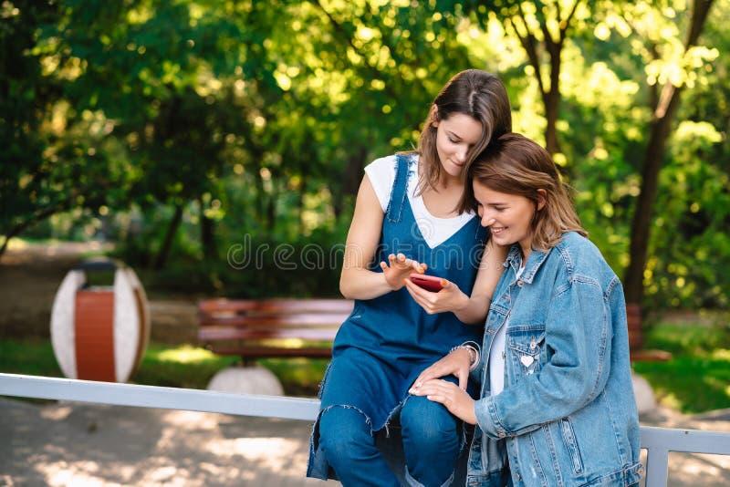 Twee vrouwelijke meisjes bekijken smartphone bij het pak royalty-vrije stock afbeeldingen