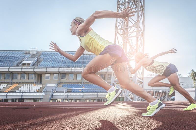 Twee vrouwelijke sprinteratleten die op de tredmolen lopen rennen tijdens opleiding in atletiekstadion stock foto