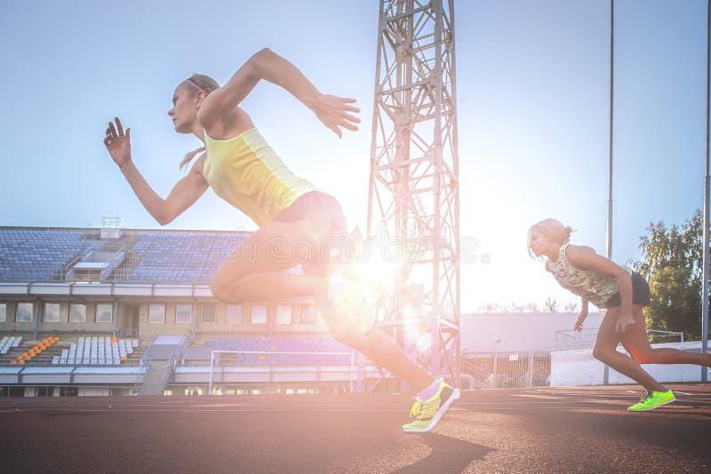 Twee vrouwelijke sprinteratleten die op de tredmolen lopen rennen tijdens opleiding in atletiekstadion stock fotografie