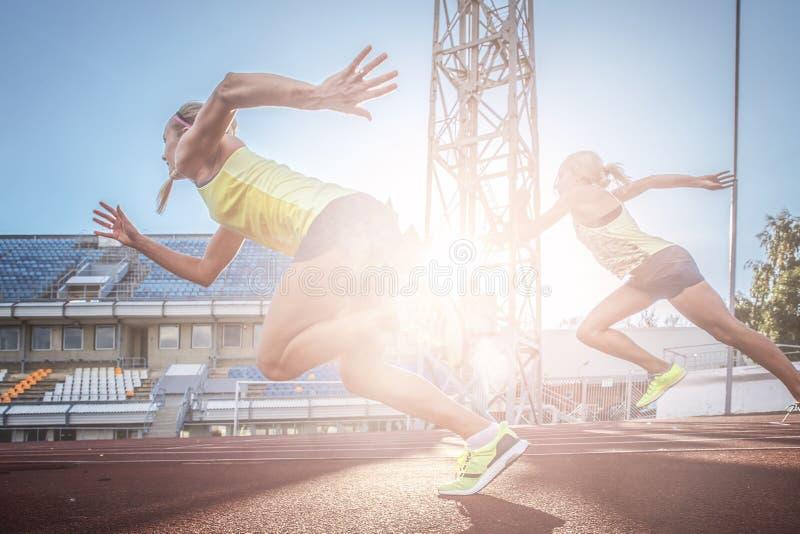 Twee vrouwelijke sprinteratleten die op de tredmolen lopen rennen tijdens opleiding in atletiekstadion royalty-vrije stock foto's
