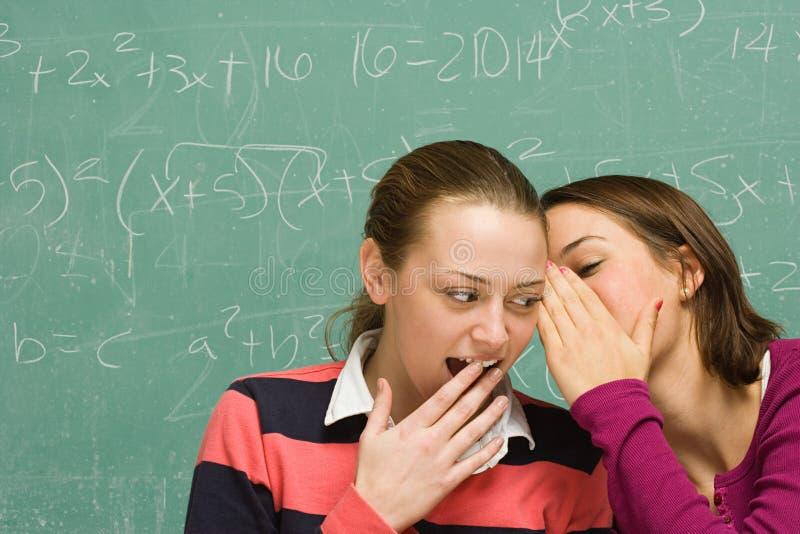 Twee vrouwelijke studenten die een geheim delen royalty-vrije stock foto's