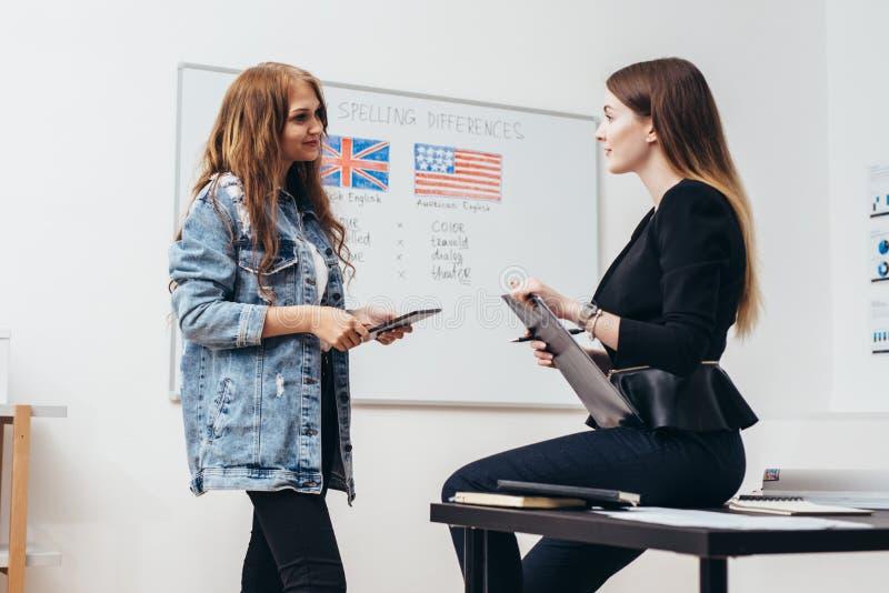 Twee vrouwelijke studenten die in klaslokaal spreken Universiteit, Engelstalige school stock afbeeldingen