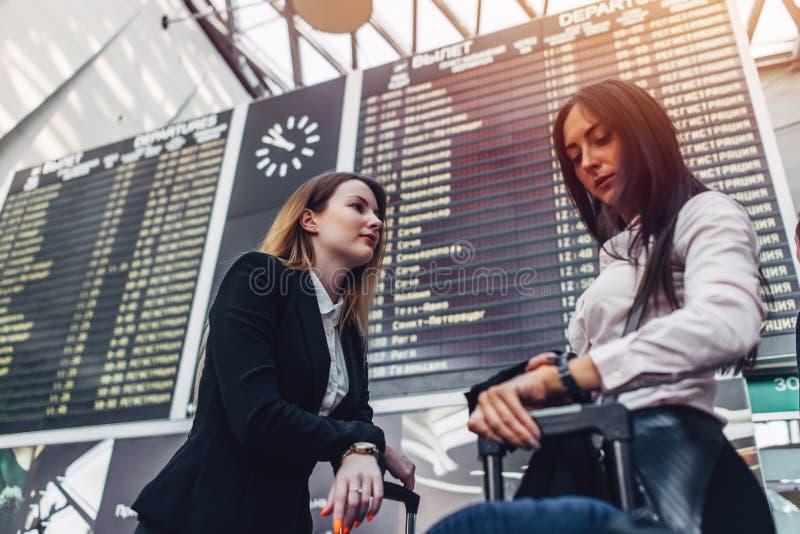 Twee vrouwelijke toeristen die zich dichtbij de vertoning van de vluchtinformatie in internationale luchthaven bevinden royalty-vrije stock foto