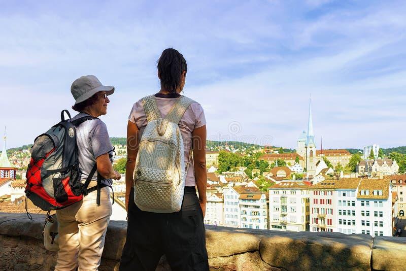 Twee vrouwelijke toeristenbackpackers die in Limmatquai van Zürich bekijken royalty-vrije stock afbeeldingen