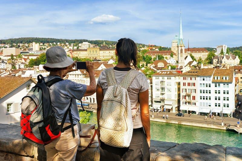 Twee vrouwelijke toeristenbackpackers die nemend foto's in Limmatquai Zürich bekijken stock foto