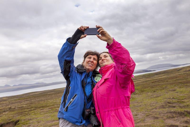Twee vrouwelijke turistvrienden die fotografen reizen nemen een selfie stock afbeelding