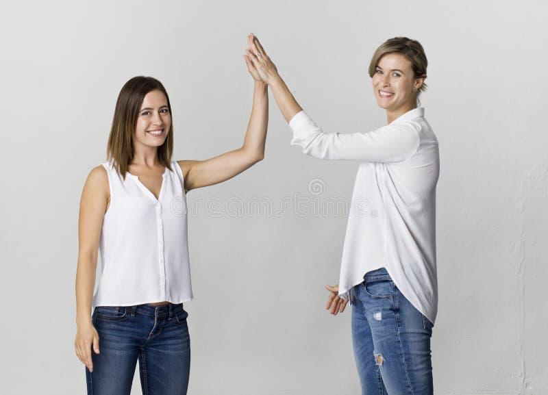 Twee vrouwelijke vrienden begroeten en hebben pret bij studiobackgro stock fotografie