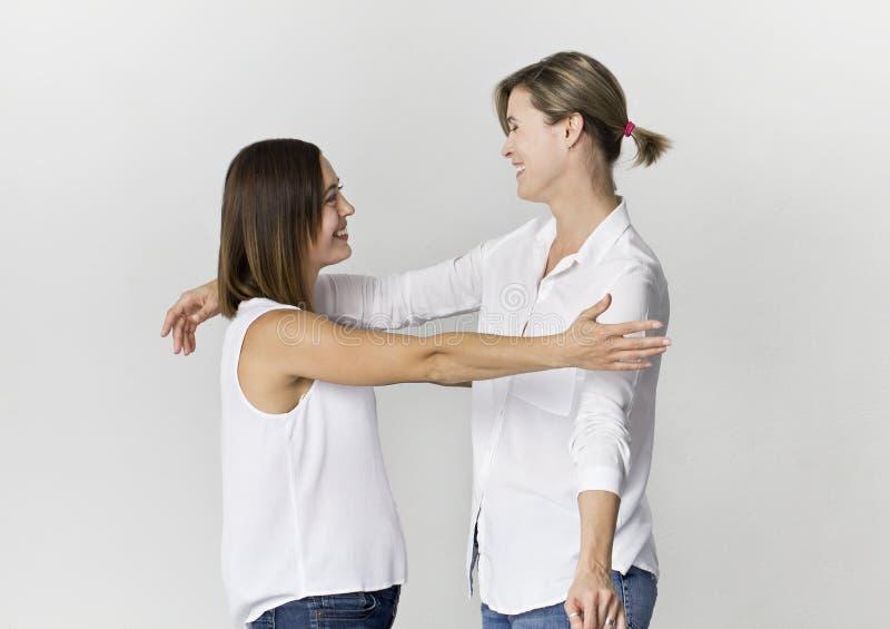 Twee vrouwelijke vrienden begroeten en hebben pret bij studiobackgro royalty-vrije stock afbeelding