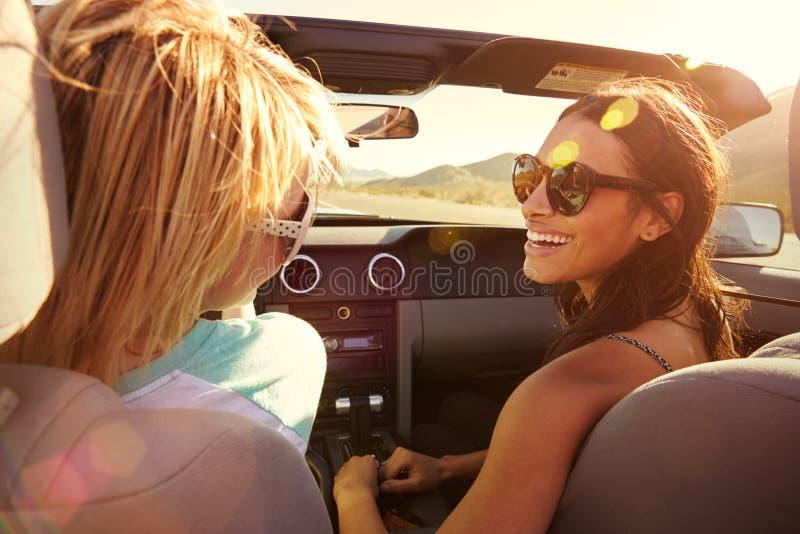 Twee Vrouwelijke Vrienden bij Wegreis het Drijven in Convertibele Auto stock afbeelding
