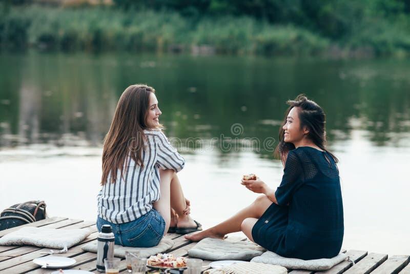 Twee vrouwelijke vrienden die bij pijler het ontspannen op meer spreken royalty-vrije stock afbeelding