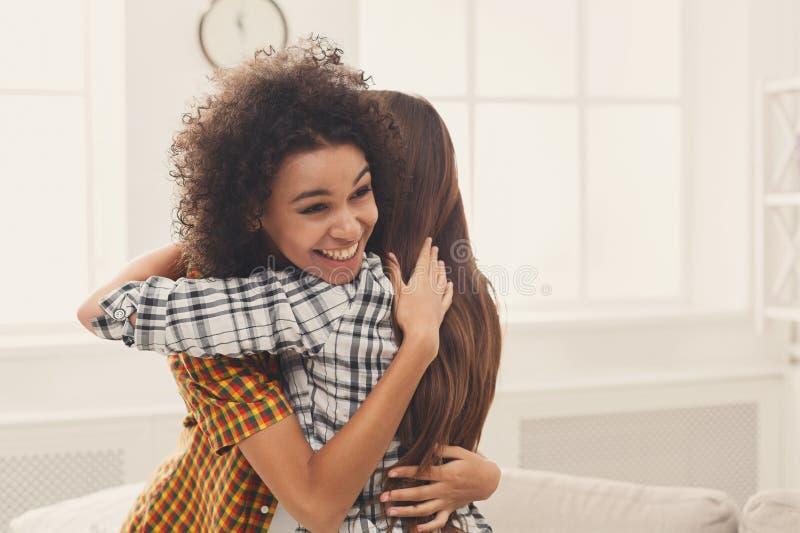 Twee vrouwelijke vrienden die elkaar thuis omhelzen royalty-vrije stock afbeelding