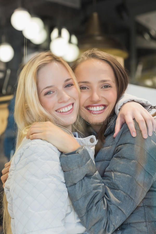 Twee vrouwelijke vrienden die met de winterkleren bij camera glimlachen royalty-vrije stock fotografie