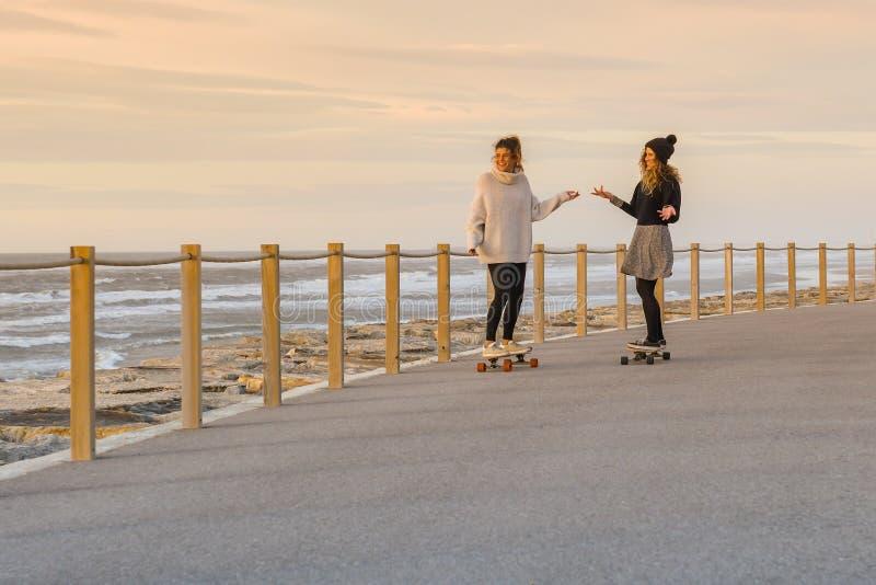 Twee vrouwelijke vrienden die met skateboard spelen royalty-vrije stock fotografie