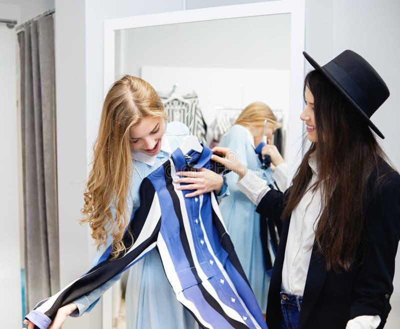 Twee vrouwelijke vrienden die op een kleding in de winkel proberen stock afbeeldingen