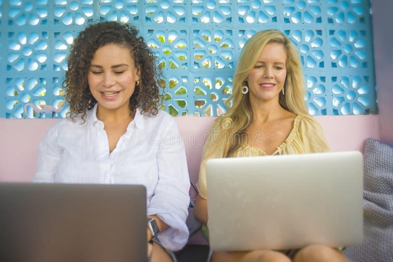 Twee vrouwelijke vrienden die in openlucht bij koele koffie met laptop computer, één Kaukasisch meisje samenwerken, andere gemeng stock afbeelding